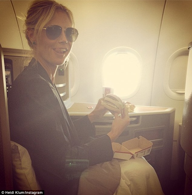 Heidi Klum about to 'eat' a McDonald's double cheeseburger travelling on a plane in first class. No doubt Ms. Klum is about to be disappointed. Source: Instagram